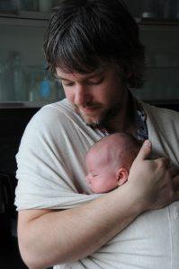 Vader draagt baby in een draagdoek